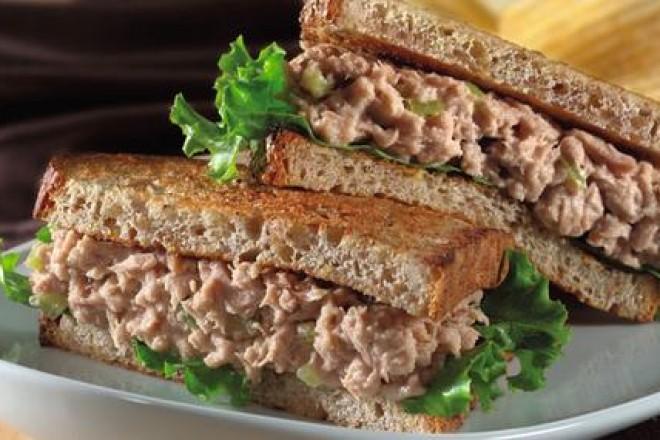 Chleb żytni z sałatą, tuńczykiem z puszki, posypane sezamem; śliwki