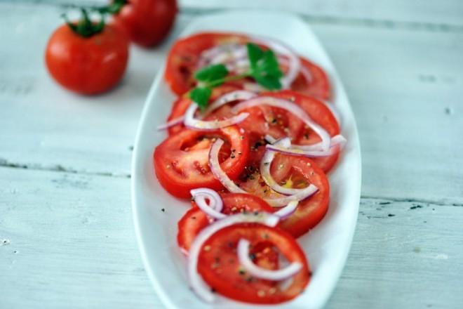 Sałatka z pomidora, cebuli i oliwy, posypana pestkami słonecznika; chleb chrupki